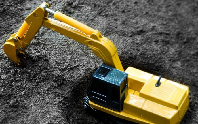 Funny wallpaper - toy excavator in a pit