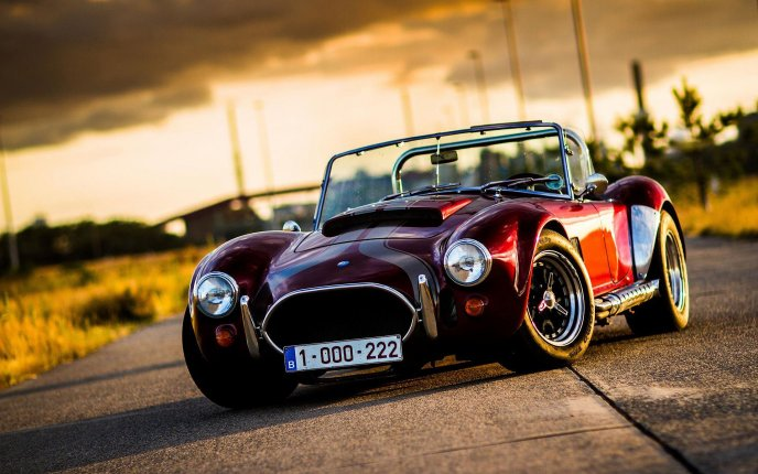 Old classic car - small AC Cobra on the road