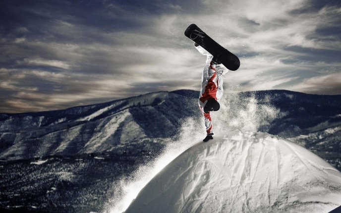 Stay in one hand on the top of the mountain with snowboard